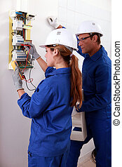 a young female electrician using an ammeter for checking an electricity meter and an older man watching her