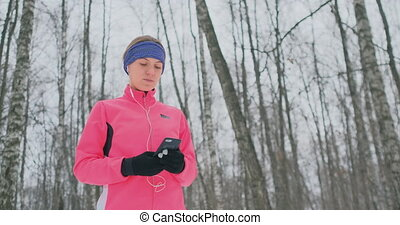 A young female on the morning jog holds in her hands a...