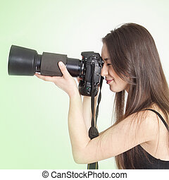 a young female photographer with a professional camera over ...