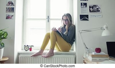 A young female student with book sitting on window sill,...