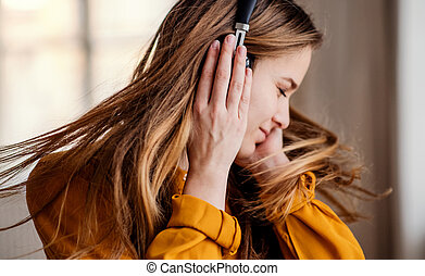 A young female student with headphones having fun.