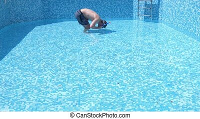 a young funny guy climbs into an empty swimming pool with a...