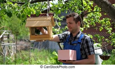 A young gardener in blue overalls feeding birds