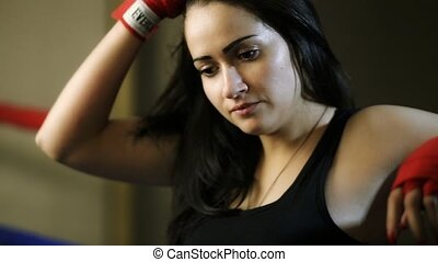 A young girl, a Latino woman, hung on the ropes of the ring, thinks, straightening her hair, looking at the ground.