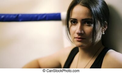 A young girl, a latino woman sits in the corner of the ring, looks in front of her, morally prepares for a fight