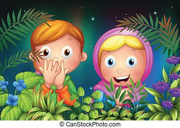 A young girl and boy hiding in the garden