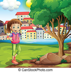 A young girl at the riverbank near the tree