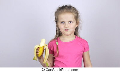 A young girl bites a banana and shows her thumb up