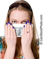 A young girl covers her face with a pack of dollars.