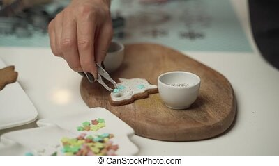 A young girl decorates ginger cookies Christmas winter evening. Woman draws Icing on honey gingerbread house. Wooden brown table. copy space. Blank biscuit gingerbread house, ready to decorate.