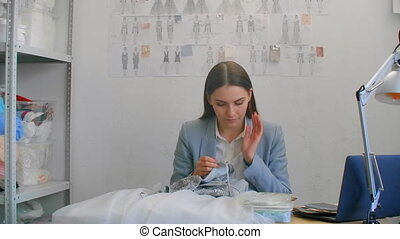 A young girl designer sewing a dress in the Studio dress. Making clothes sewing beads and jewelry. Seamstress decorates a dress in the Studio