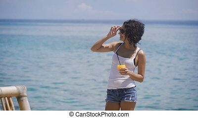 A young girl dressed in a white T-shirt and short denim shorts standing next to the blue ocean.