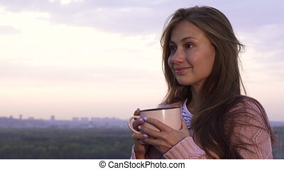 A young girl drinks a warm drink and enjoys the sunset