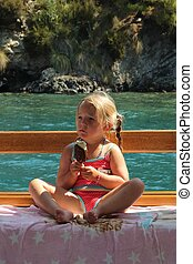 A young girl eating an ice cream on a boat while on...