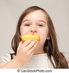 A young girl enjoys a donut