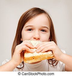 A young girl enjoys a sandwhich consisting of wholemeal bread.