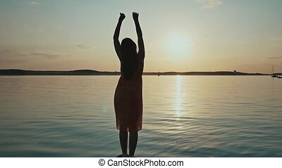 A young girl enjoys the sunset raising her hands and standing on the shore of the lake