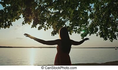 A young girl enjoys the sunset raising her hands and standing on the shore of the lake.