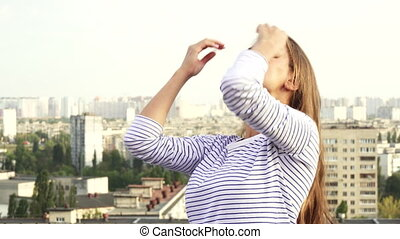 A young girl enjoys the weather while standing on the roof