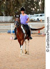 girl getting a horseback riding lesson