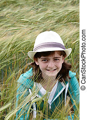 A young girl hiding in a corn field