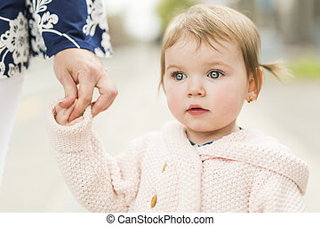 young girl holding hands with her parent outside