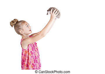 A young girl holding her pet hedgehog up in the air