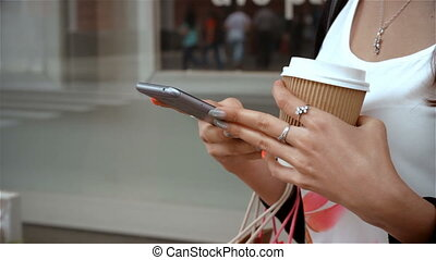a young girl holds a cup of coffee and stares into the phone