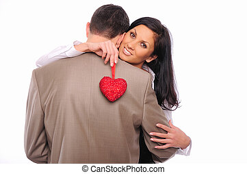 young girl hugs her man and holding a red heart
