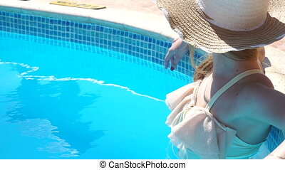 a young girl in a bathing suit and hat stands in pool unscrewing the head back