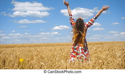 a young girl in a beautiful dress standing in a field with wheat