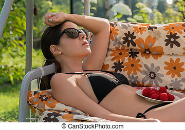 A young girl in a black swimsuit and glasses with a bowl of berries rests on the country swings