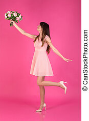 A young girl in a festive dress is catching a bouquet of flowers on pink