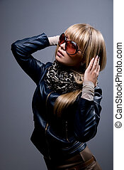 A young girl in a leather jacket and dark glasses looking to the side. Isolated on a dark background