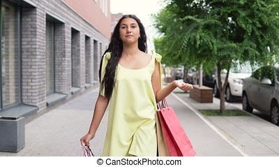 A young girl in a long yellow dress goes around the city after shopping having a good mood. 4K