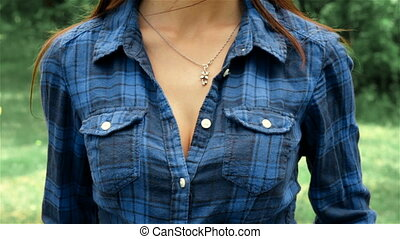 a young girl in a Plaid Shirt standing and buttons - a young...