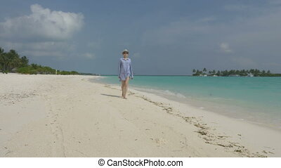 A young girl in a shirt and hat walks along the beach of white sand by the ocean. Maldives