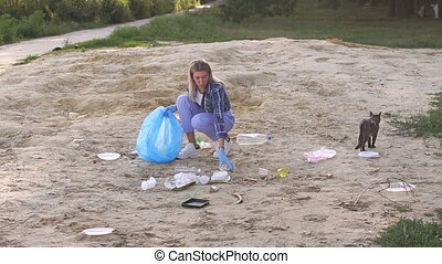 A young girl in a shirt collects trash on the beach in a park near a lake.