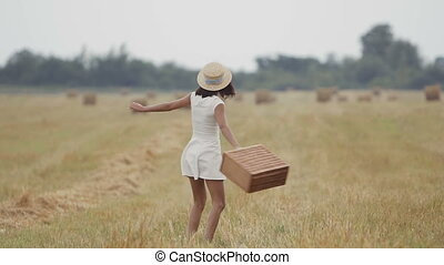 A young girl in a straw hat and in a white dress happily runs around the field. The girl in her arms holds a straw basket. Sunset