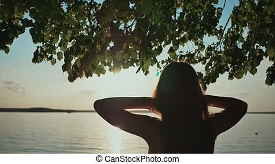 A young girl in a summer dress is enjoying the sunset on the lake shore.