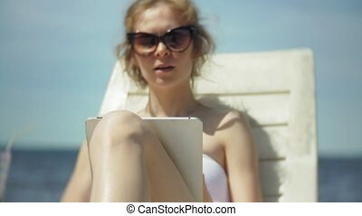A young girl in a white bikini lies and tans on a deckchair on a sea sandy beach and is working on a tablet