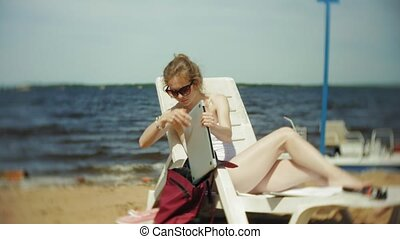 A young girl in a white bikini lies and tans on a deckchair on a sea sandy beach and is working on a laptop