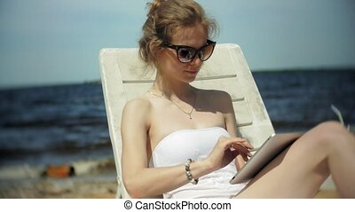 A young girl in a white bikini lies and tans on a deckchair...