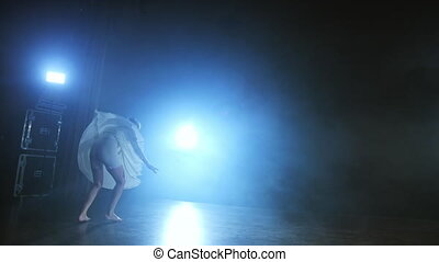 a young girl in a white dress dances a modern ballet on the...
