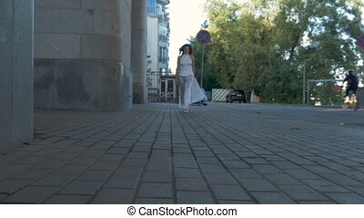 A young girl in a white suit runs along the embankment.