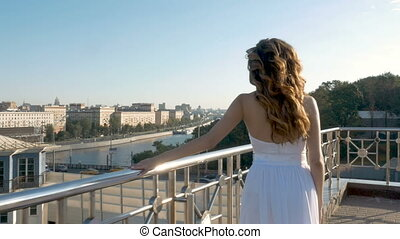 A young girl in a white suit walks on the observation deck.