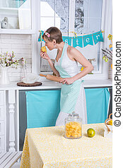 A young girl in an apron in the kitchen