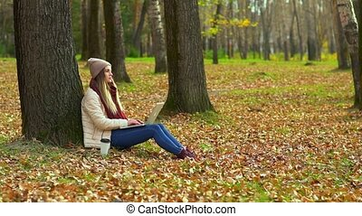 A young girl in an autumn Park near a tree, typing in a laptop, working.