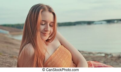 A young girl in an orange dress poses at sunset on the beach.