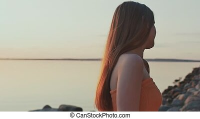 A young girl in an orange dress poses at sunset on the beach and plays with her hair.